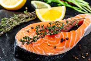 Close-up of a slice of salmon with fresh thyme and lemon slices