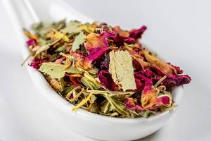 Close-up of Australian green tea with flower petals in a white spoon (Flip 2020)