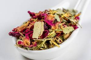 Close-up of Australian green tea with flower petals in a white spoon