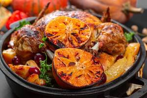 Close-up of baked chicken with oranges and potatoes on a baking sheet