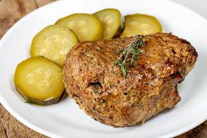 Close-up of baked meat with sliced pickles (Flip 2020)