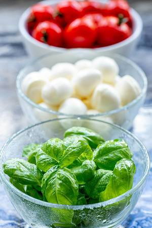 Close-up of Basil leaves and tomatoes with mozzarella behind (Flip 2019) (Flip 2019)