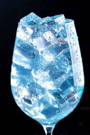 Close-up of blue cocktail with ice cubes in the glass (Flip 2019)