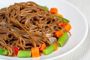 Close-up of buckwheat soba noodles with asparagus, carrots and sweet peppers