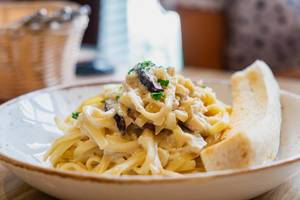 Close up of carbonara with sliced bread on side