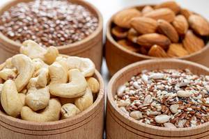 Close-up of cashew nuts, almonds and various seeds in wooden bowls
