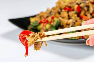 Close-up of chicken with vegetables in spicy sauce and chopsticks. The concept of Chinese food (Flip 2019)