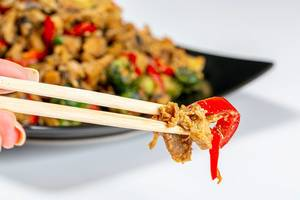 Close-up of chicken with vegetables in spicy sauce and chopsticks. The concept of Chinese food