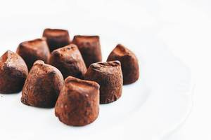 Close up of chocolate truffles on white background