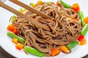 Close up of chopsticks and soba with vegetables