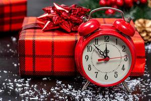 Close up of Christmas background with red alarm clock and gift boxes