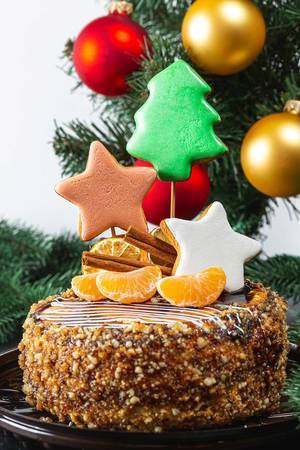 Close-up of Christmas cake with gingerbread and tangerines on the background of the Christmas tree (Flip 2019)
