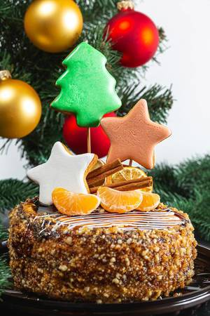 Close-up of Christmas cake with gingerbread and tangerines on the background of the Christmas tree