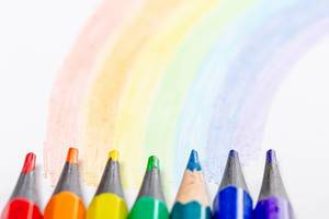 Close-up of colored pencils and a painted rainbow on a white background (Flip 2019)
