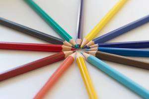 Close Up of Colorful Pencils pointing to each other and creating a circle on white Background