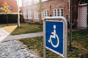 Close up of disabled sign on the street. Building in the background
