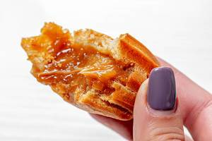 Close up of eclair with condensed milk in a woman