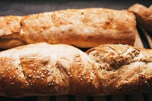 Close up of french baguette with sesame on dark background