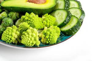 Close-up of fresh slices of romanesco cabbage, cucumber and avocado on a blue plate