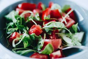 Close up of fresh summer salad wih tomatoes and arugula