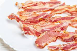 Close-up of fried bacon slices on a white plate