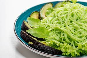 Close up of green spaghetti with avocado slices and basil