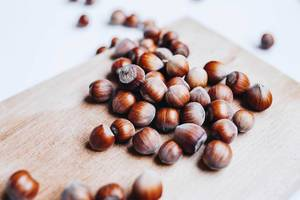 Close up of hazelnuts on board. White background