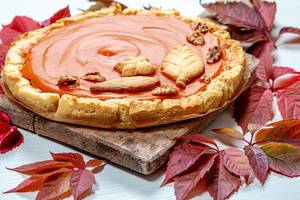 Close - up of homemade pumpkin pie on an old kitchen Board with colorful autumn leaves. The concept of the autumn holidays (Flip 2019)