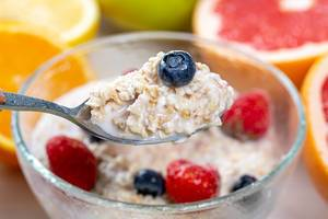 Close-up of oatmeal with berries and milk in a spoon