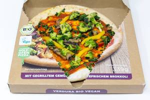 Close-up of open package of followfood vegan pizza with grilled veggies, fresh broccoli and spelt dough