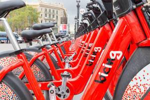 "Close-up of red bikes in a row to rent from ""bicing"" in Barcelona, Spain at Plaça de Catalunya"