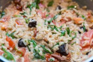 Close-up of Risotto with dried tomatoes, olives, walnuts and Italian hard cheese