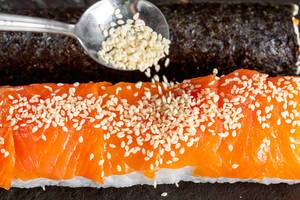 Close-up of sesame pours on sushi roll with salmon
