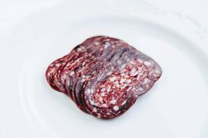 Close up of sliced salami on white background