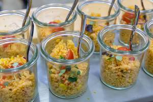 Close-up of small jars filled with vegan couscous salad made with tomato, red onion and corn at the BarCamp in Bonn