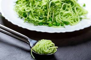 Close up of spinach spaghetti wound on a fork