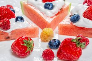 Close-up of strawberries, raspberries, blueberries and watermelon-fruit dessert with cream