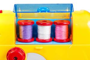 Close up of three spools of thread in a toy sewing machine