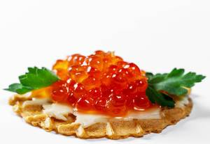 Close-up of waffle with red caviar, cheese and herbs