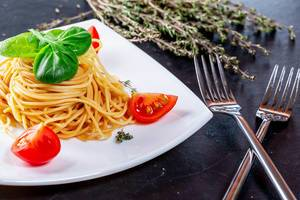 Close Up Photo of a Plate of Spaghetti with Cherry Tomatoes, Basil and Rosmary next to two Forks