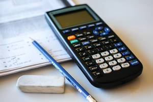 Close Up Photo of Calculator, Pencil and Eraser with Mathematics Exercises on White Table