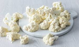 Close Up Photo of Cauliflower on Cutting Board and Wooden Table