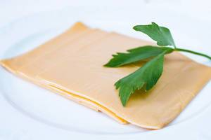 Close Up Photo of Cheddar Cheese Slices on a White Plate on White Background