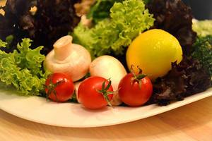 Close Up Photo of Cherry Tomatoes, Mushrooms, Lemon and Lettuce on a Plate
