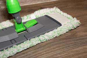 Close Up Photo of Cleaning Mop on a Brown Wooden Floor