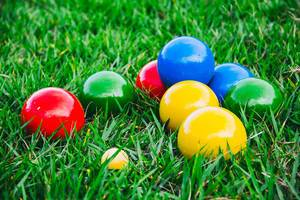 Close Up Photo of Colorful Italian Outdoor Game Bocce Balls laying on lawn