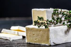 Close Up Photo of Cut Brie Cheese with Fresh Thyme and Brie Cheese Slices on Dark Background