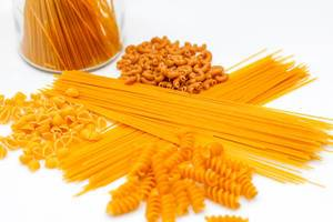 Close Up Photo of different kinds of Pasta like Spaghetti, Fusilli and Macaroni on white Background