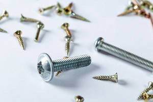 Close Up Photo of different sized Screws on White Background