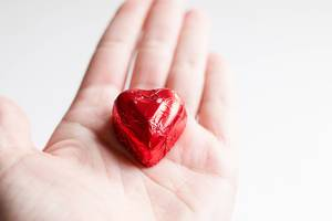 Close Up Photo of Heart shaped Chocolate wrapped in Red Foil laying on a Hand